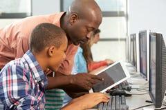 使用数字式片剂的老师帮助的男孩在计算机类 免版税库存照片