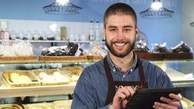 使用数字式片剂的英俊的专业男性面包师在他的商店 库存照片
