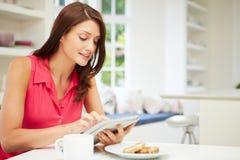 使用数字式片剂的西班牙妇女在厨房 免版税库存图片