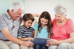 使用数字式片剂的资深夫妇有他们的盛大孩子的 免版税库存照片
