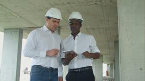 使用数字式片剂的非裔美国人的工程师和caucasine建筑师和头戴安全帽在建造场所 股票录像