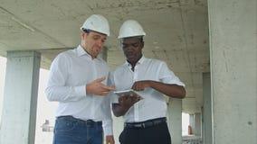 使用数字式片剂的非裔美国人的工程师和caucasine建筑师和头戴安全帽在建造场所 库存照片