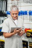 使用数字式片剂的顾客在硬件商店 库存图片