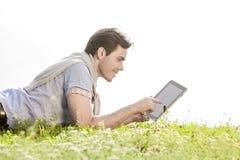 使用数字式片剂的年轻人侧视图,当说谎在草反对清楚的天空时 免版税库存照片
