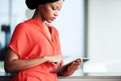使用数字式片剂的年轻黑人女学生在现代环境 免版税库存照片