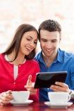 使用数字式片剂的夫妇在咖啡馆 免版税库存照片