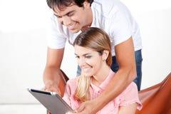 使用数字式片剂的年轻夫妇 免版税库存照片