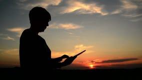 使用数字式片剂计算机的妇女为浏览的互联网 与站立在日落的现代小配件的女性剪影 股票录像