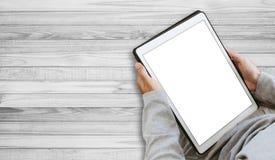 使用数字式片剂,在屏幕上的拷贝空间的人,在木地板上 免版税图库摄影