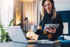 使用数字式片剂,年轻女实业家站立在计算机,饮用的咖啡前面的近的桌, 女孩在家工作 免版税图库摄影