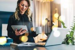 使用数字式片剂,年轻女实业家站立在计算机,饮用的咖啡前面的近的桌, 女孩在家工作 库存图片