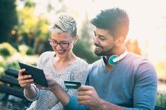 使用数字式片剂,年轻混合的族种夫妇做着在网上购物 免版税库存图片
