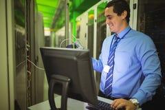 使用数字式缆绳分析仪的技术员,当研究个人计算机时 免版税库存图片
