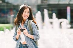 使用数字式袖珍相机和微笑的年轻美丽的亚裔背包旅客妇女,看拷贝空间 免版税库存图片
