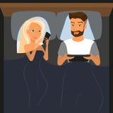 使用数字式设备的愉快的夫妇在床上在晚上 库存照片