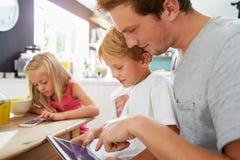 使用数字式设备的父亲和孩子在早餐桌 免版税库存图片