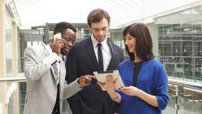 使用数字片剂的多种族商人在见面在现代办公室大厅 影视素材