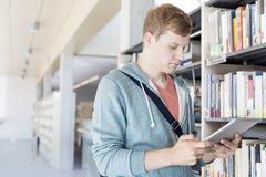 使用数字片剂的学生,当支持书架在图书馆时 免版税库存图片