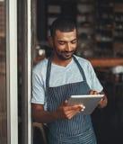 使用数字片剂的年轻男性企业家在咖啡馆entranc 免版税库存照片