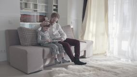 使用数字片剂的微笑的愉快的父亲和儿子坐长沙发在大客厅 愉快的家庭花费时间 影视素材