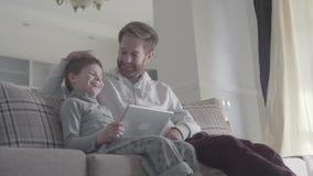 使用数字片剂的微笑的愉快的父亲和儿子坐长沙发在大客厅 愉快的家庭花费时间 股票视频