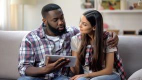 使用数字片剂的愉快的年轻夫妇在家,在网上预定旅馆,假期 库存图片