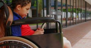 使用数字片剂的残疾非裔美国人的男小学生侧视图在学校走廊4k 股票视频
