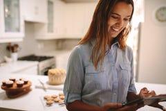 使用数字片剂的点心师在厨房里 库存图片