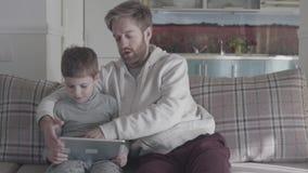 使用数字片剂的父亲和儿子坐长沙发在大客厅 爸爸教他的孩子 愉快的家庭花费 影视素材