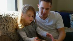 使用数字片剂的父亲和女儿在客厅 影视素材
