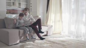 使用数字片剂的爸爸和儿子坐长沙发在大客厅 愉快的家庭一起花费时间 爸爸 股票视频