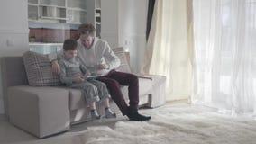 使用数字片剂的爸爸和儿子坐长沙发在大客厅 愉快的家庭一起花费时间 影视素材