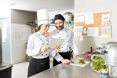 使用数字片剂的西班牙厨师在厨房里 免版税库存图片