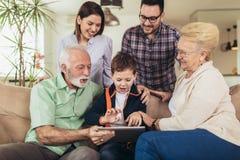 使用数字片剂,三一代家庭在家一起消费时间 库存照片