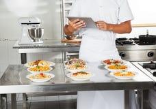使用数字计算机的厨师在厨房 免版税库存照片