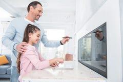 使用新技术的好宜人的父亲和女儿 库存图片
