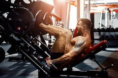 使用新闻机器的人在健身俱乐部 做在它的脚的大力士一锻炼在模拟器 免版税库存照片