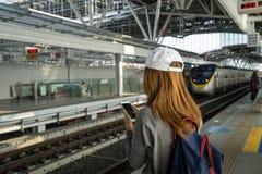 使用旅行app的少妇旅客在巧妙的电话 图库摄影