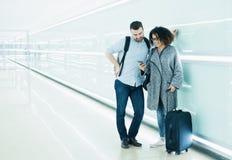 使用旅行app,准备好的夫妇去休假 库存照片