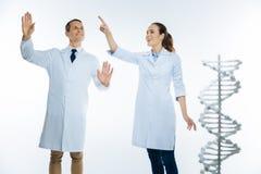 使用无形的屏幕的光芒四射的医疗专家,当与脱氧核糖核酸一起使用时 库存图片