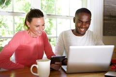 使用无线技术的混合的族种夫妇在家 免版税库存图片