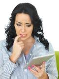 使用无线片剂的害怕急切谨慎年轻西班牙妇女 免版税库存图片