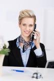 使用无线电话的接待员在书桌 免版税库存照片