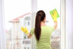 使用旧布的少妇,当清洗窗口时 库存照片