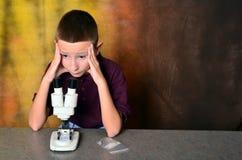 使用显微镜的年轻男孩 库存照片