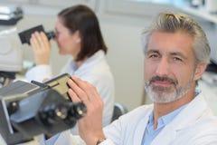 使用显微镜的成熟男性研究员在医学实验室 图库摄影