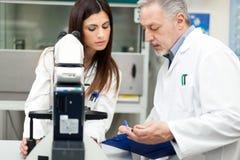 使用显微镜的科学家在实验室 免版税库存照片