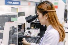 使用显微镜的科学家在实验室 图库摄影