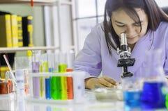 使用显微镜,化工测试在实验室,改进的安全产品概念的化学家妇女在适用于消费者前 免版税库存图片