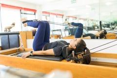 使用普拉提改革者机器的灵活的女性在健身房 库存照片